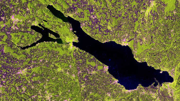 This satellite image of Lake Constance was acquired on May 10, 2014 in 'interferometric wide swath mode' and in dual polarization. The radar instrument gathers information in either horizontal or vertical radar pulses, and colors were assigned to the different types. In this image, buildings generally appear pink, while vegetation is green. Areas with lowest reflectivity in all polarisations appear very dark, like the water. Source: ESA.