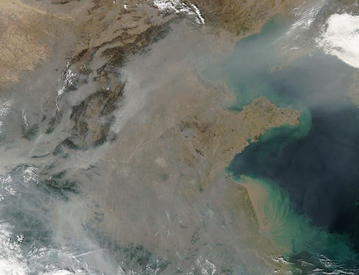 This true-color image over eastern China was acquired by the Moderate Resolution Imaging Spectroradiometer (MODIS), flying aboard NASA's Aqua satellite, on Oct. 16, 2002. The scene reveals dozens of fires burning on the surface (red dots) and a thick pall of smoke and haze (greyish pixels) filling the skies overhead. Notice in the high-resolution version of this image how the smog fills the valleys and courses around the contours of the terrain in China's hilly and mountainous regions. The terrain higher in elevation is less obscured by the smog than the lower lying plains and valleys in the surrounding countryside. This scene spans roughly from Beijing (near top center) to the Yangtze River, the mouth of which can be seen toward the bottom right. Toward the upper right corner, the Bo Hai Bay is rather obscured by the plume of pollution blowing eastward toward Korea and the Pacific Ocean. Toward the bottom right, the Yangtze River is depositing its brownish, sediment-laden waters into the Yellow Sea.