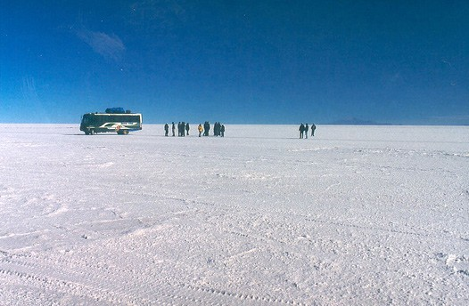 Tourists and a tour bus parked on the salt flat. The picture gives an idea of how flat Salar de Uyuni is.