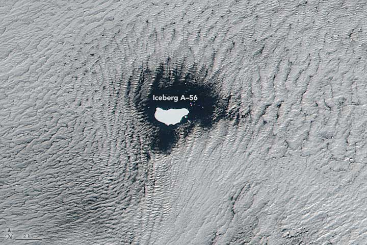 A satellite captured an image of low stratus clouds framing iceberg A-56 as it drifted in the South Atlantic Ocean on June 1, 2016. NASA image by Jeff Schmaltz, LANCE/EOSDIS Rapid Response. Caption by Kathryn Hansen