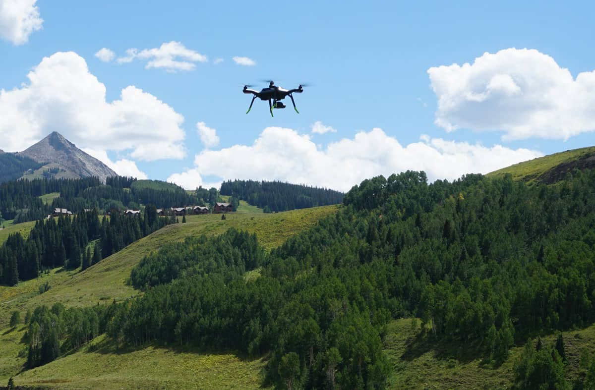 A drone hovering above a hilly grass area.