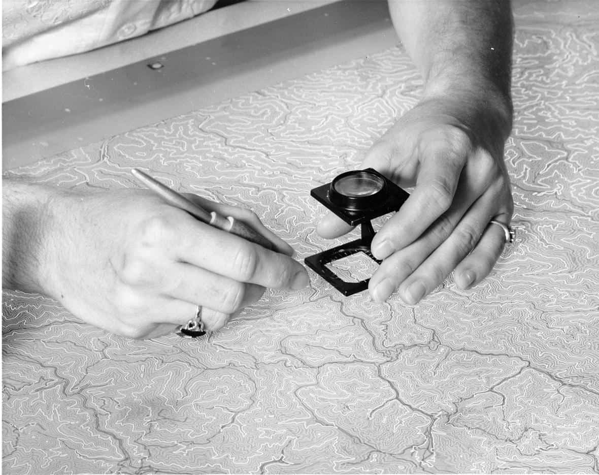 Before the use of computer cartography, mapmaking was a manual process.  Scribing of the intermediate contours for a USGS topographic map using a freehand scriber in 1957. Photo: U.S. Geological Survey. Public domain.