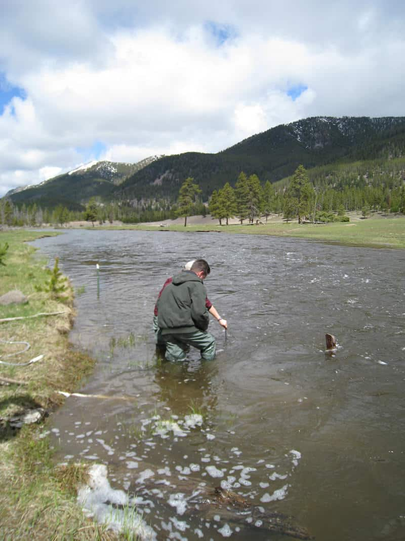 USGS employees deploys a water conductivity/temperature/depth probe (AquaTroll) for a temporary study along the Madison River, Yellowstone.