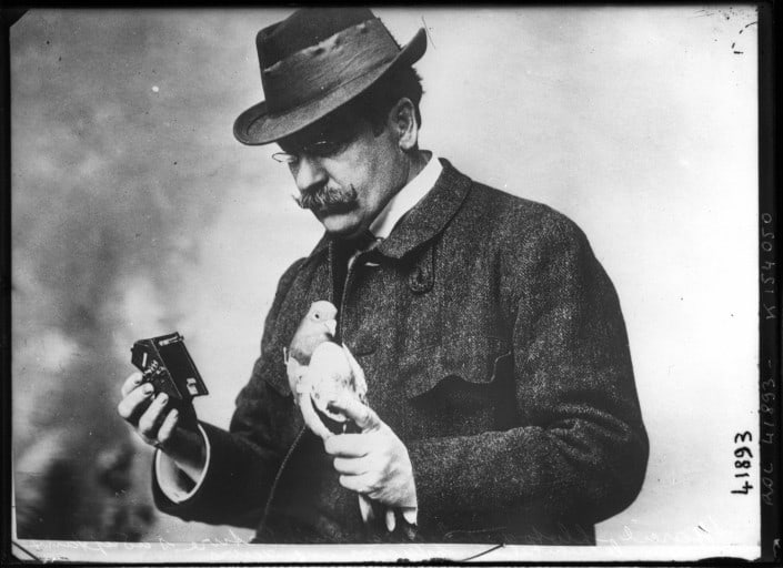 Julius Neubronner holding a homing pigeon and one of his cameras, 1914.