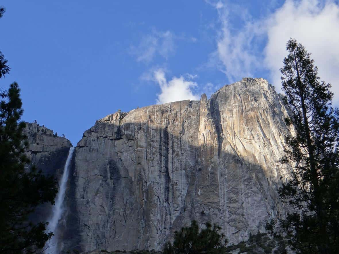 A large pinnacle may be seen adjacent to Yosemite Falls. Pinnacles form as the granite is weathered away via ice, water, or plant growth. Photo: Alex Demas, USGS. Public domain.