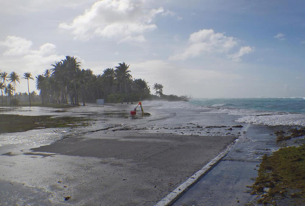 Rising sea levels will disproportionately affect low-lying coastal areas. Waves wash over a road on Roi-Namur Island, Kwajalein Atoll in the Republic of the Marshall Islands, during a particularly high tidal event. Image: Peter Swarzenski, USGS, public domain.