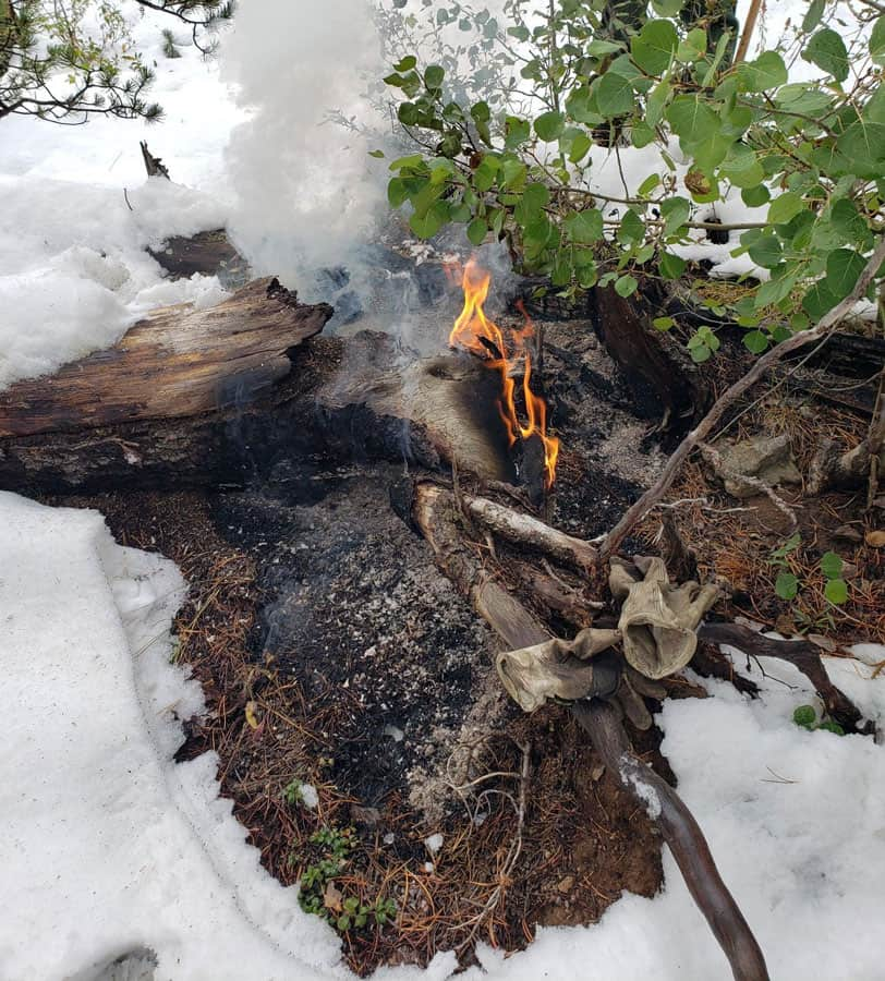 A log burning amid the snow in September.  Cameron Fire photo from InciWeb.