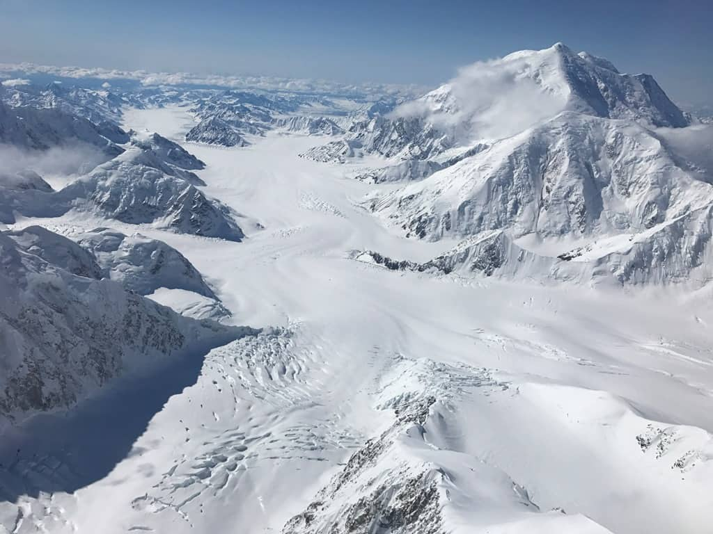 View down the Kahiltna Glacier, witih Mount Crosson and Mount Foraker to the right. In the center of the image is the confluence of the main Kahiltna and the Northeast Fork, which is the more crevassed leg on the bottom left. NPS Photo/Tucker Chenoweth, public domain.