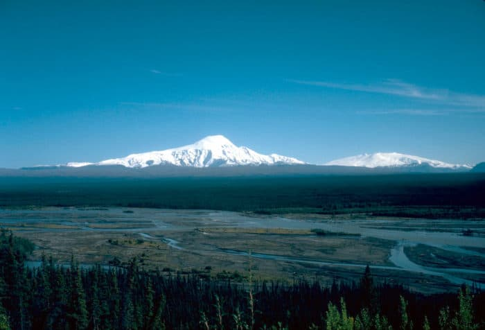 View, looking southeast, of 4,949-m (16,237 ft)-high Mount Sanford (left) and 4,317-m (14,163 ft)-high Mount Wrangell (right) on the skyline. Photograph by D. Richter, U.S. Geological Survey, August 1981, public domain.