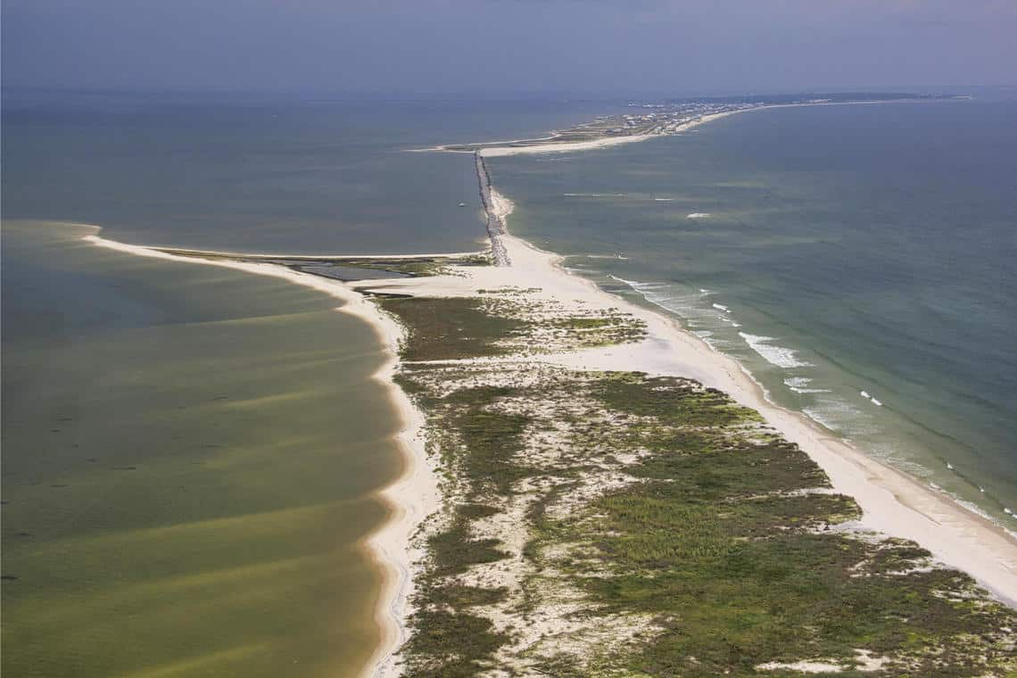 An aerial view of Dauphin Island, Alabama, shows a thin strip of road partially covered by sand, with undeveloped beach in the foreground and developed beach in the background.  Photo: Karen Morgan, USGS. Public domain.