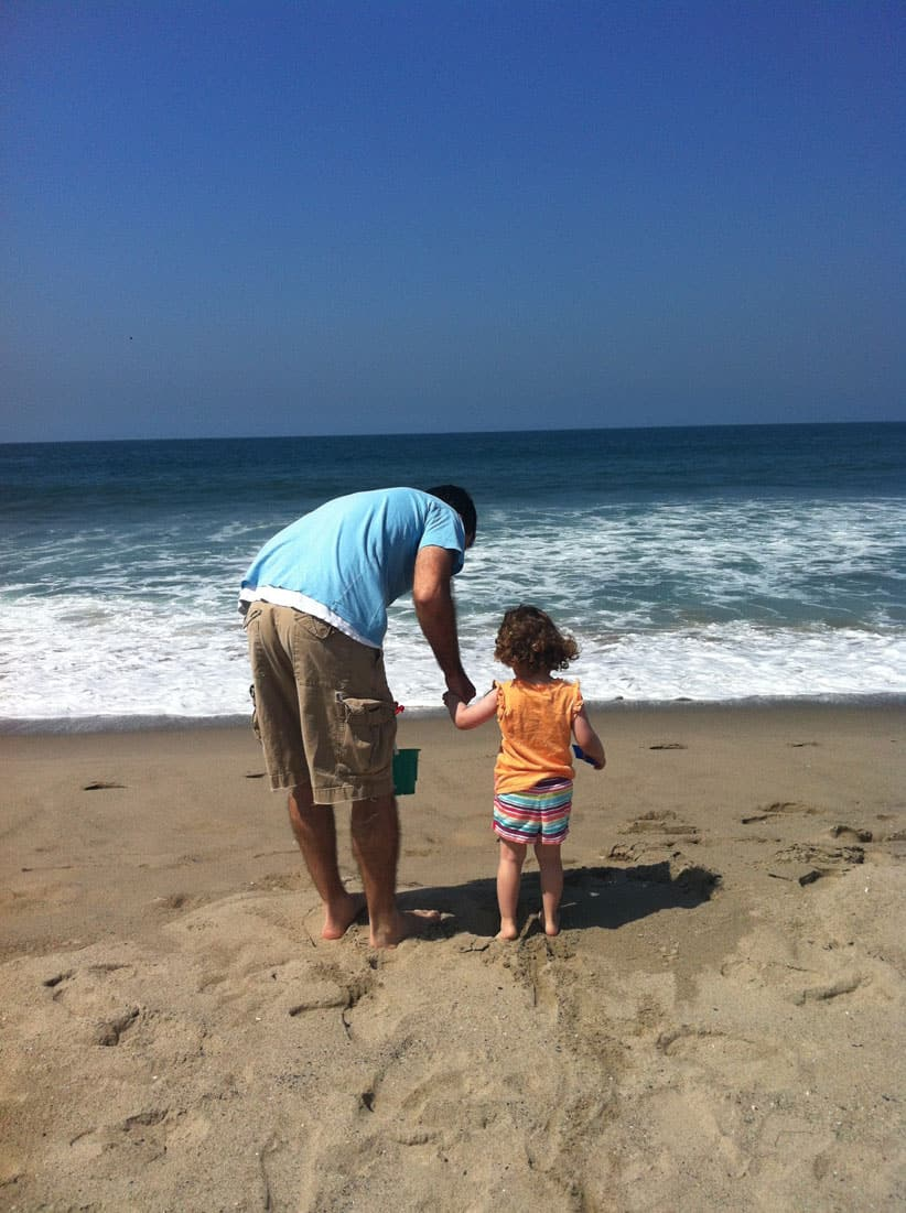 A father and daughter look out at the Pacific Ocean.