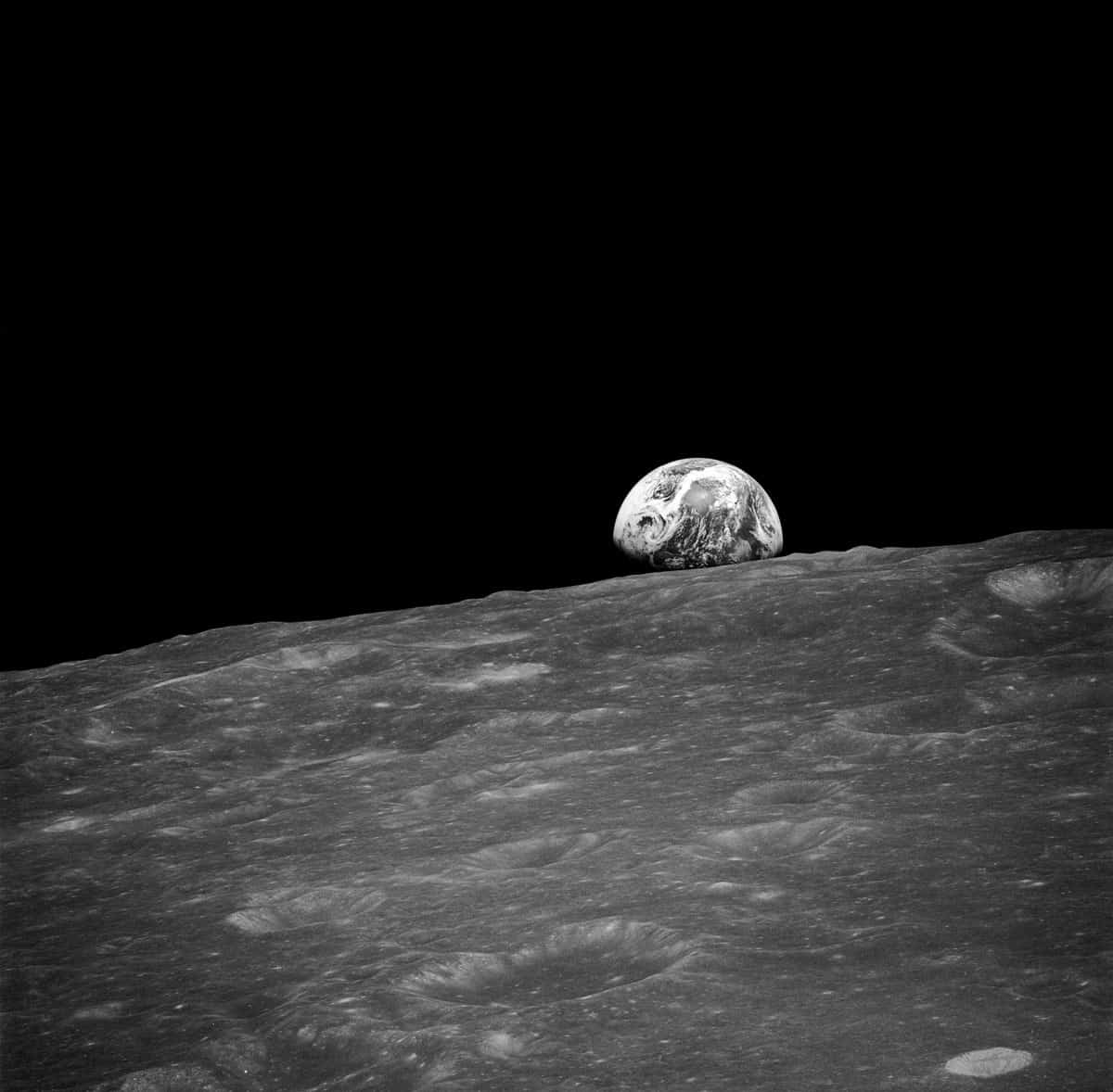 A black and white photograph of the Earth with the Moon in the foreground captured by an astronaut onboard Apollo 8, December 24, 1968.
